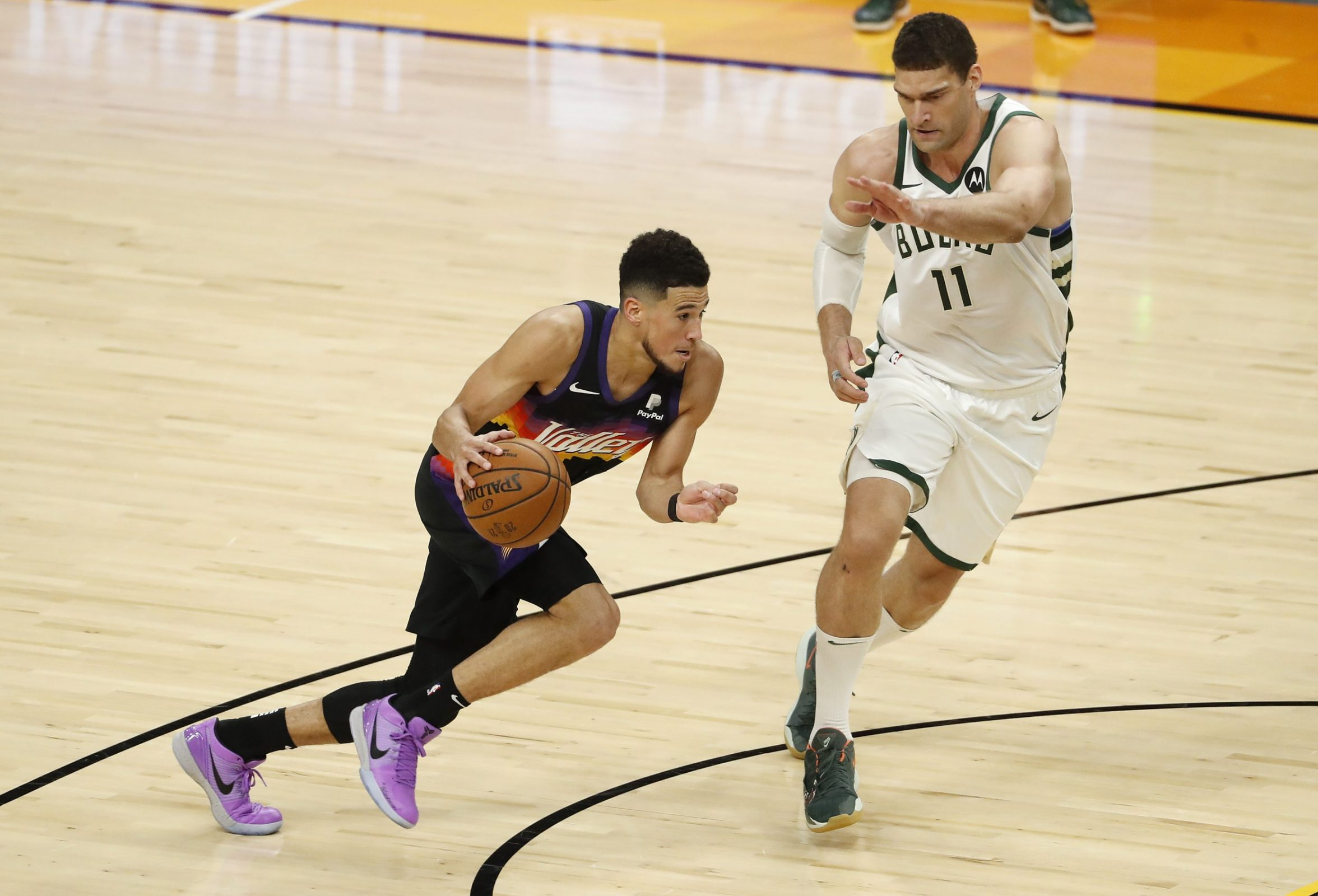 Brook Lopez tries and fails to guard Devin Booker.