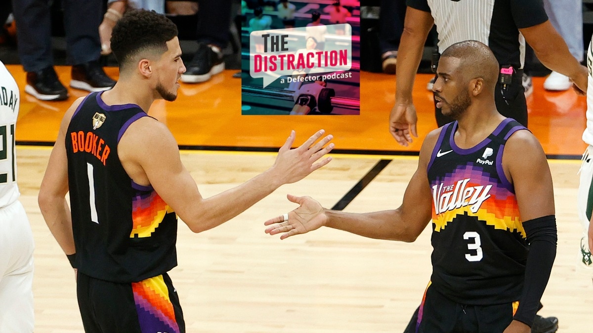 Devin Booker and Chris Paul high-five at the end of Phoenix's victory in Game 1 of the NBA Finals