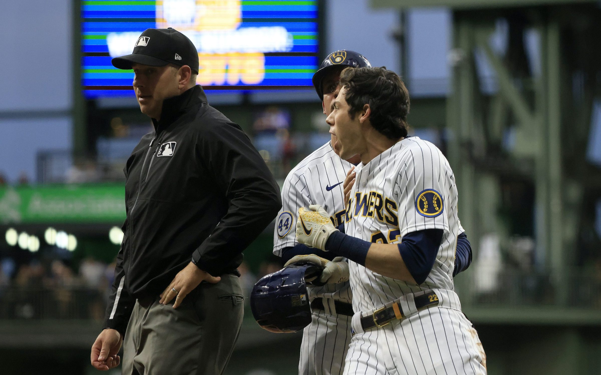Christian Yelich #22 of the Milwaukee Brewers is held back by Quintin Berry #23 of the Milwaukee Brewers after being ejected from the game by umpire John Libka #84 during the sixth inning at American Family Field on July 10, 2021 in Milwaukee, Wisconsin.