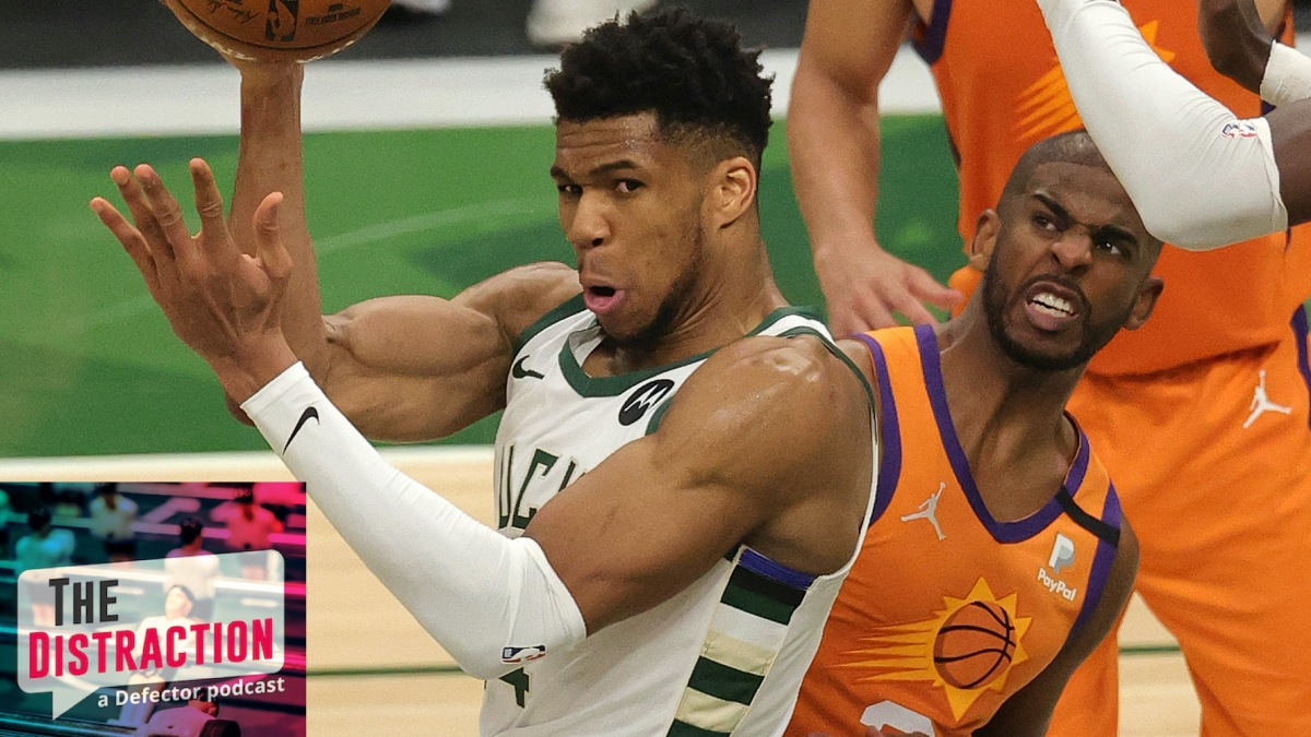 Giannis Antentokounmpo attempts a pass while being fouled by Chris Paul in Game 4 of the NBA Finals