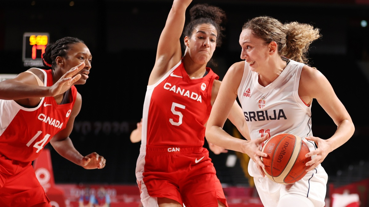 Aleksandra Crvendakic #11 of Team Serbia drives to the basket against Kayla Alexander #14 and Kia Nurse #5 of Team Canada during the first half of the Women's Preliminary Round Group A game on day three of the Tokyo 2020 Olympic Games at Saitama Super Arena on July 26, 2021 in Saitama, Japan.