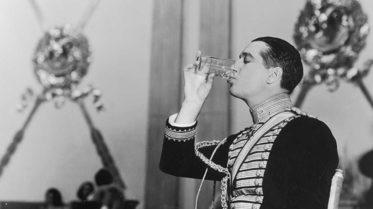 1934: Profile view of French actor Maurice Chevalier drinking a glass of water while seated in a folding chair on the set of director Ernst Lubitsch's film, 'The Merry Widow'. Chevalier wears a military uniform.