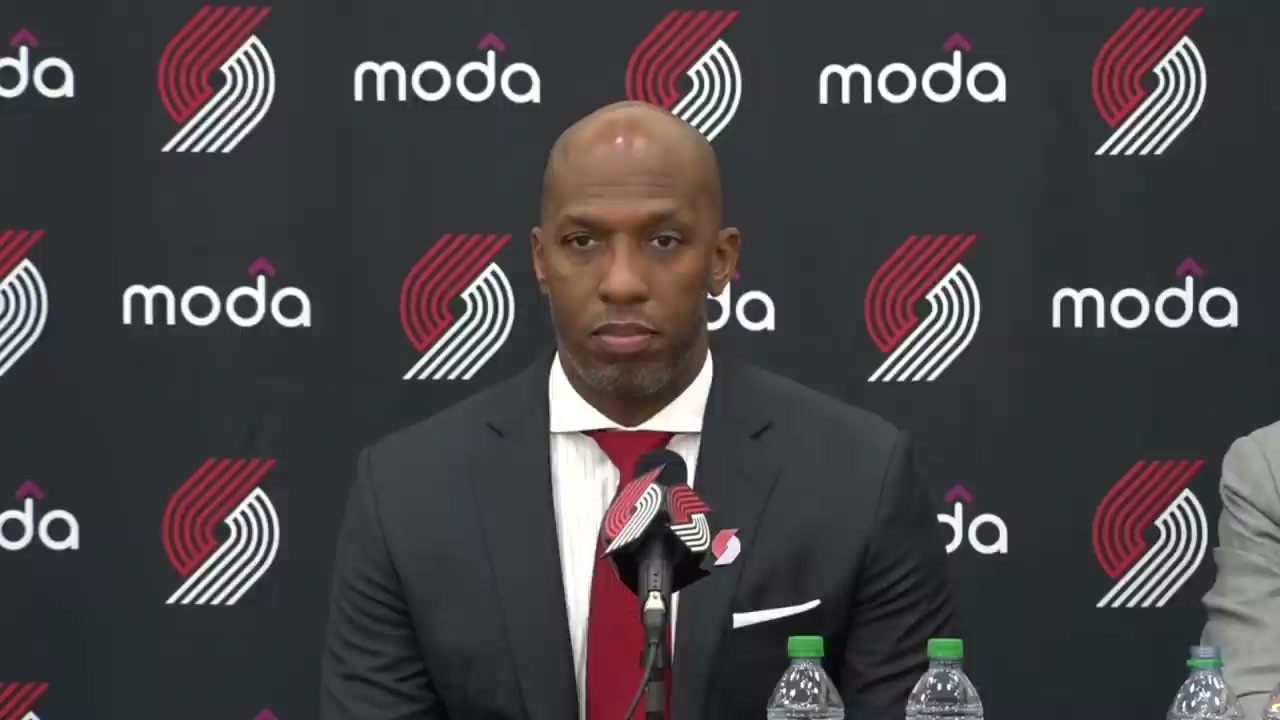 A photo of new Portland Trail Blazers head coach Chauncey Billups. He is wearing a suit and tie in Blazers colors. Behind him is a backdrop with the Blazers logo.