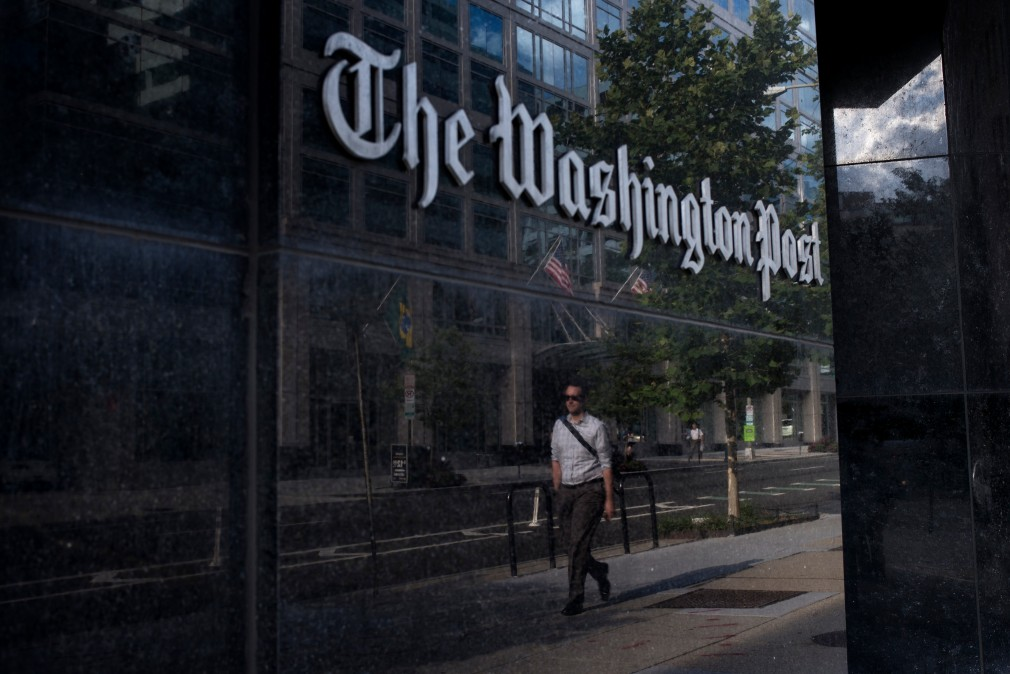 A man walks past The Washington Post on August 5, 2013 in Washington, DC after it was announced that Amazon.com founder and CEO Jeff Bezos had agreed to purchase the Post for USD 250 million. Multi-billionaire Bezos, who created Amazon, which has soared in a few years to a dominant position in online retailing, said he was buying the Post in his personal capacity and hoped to shepherd it through the evolution away from traditional newsprint.