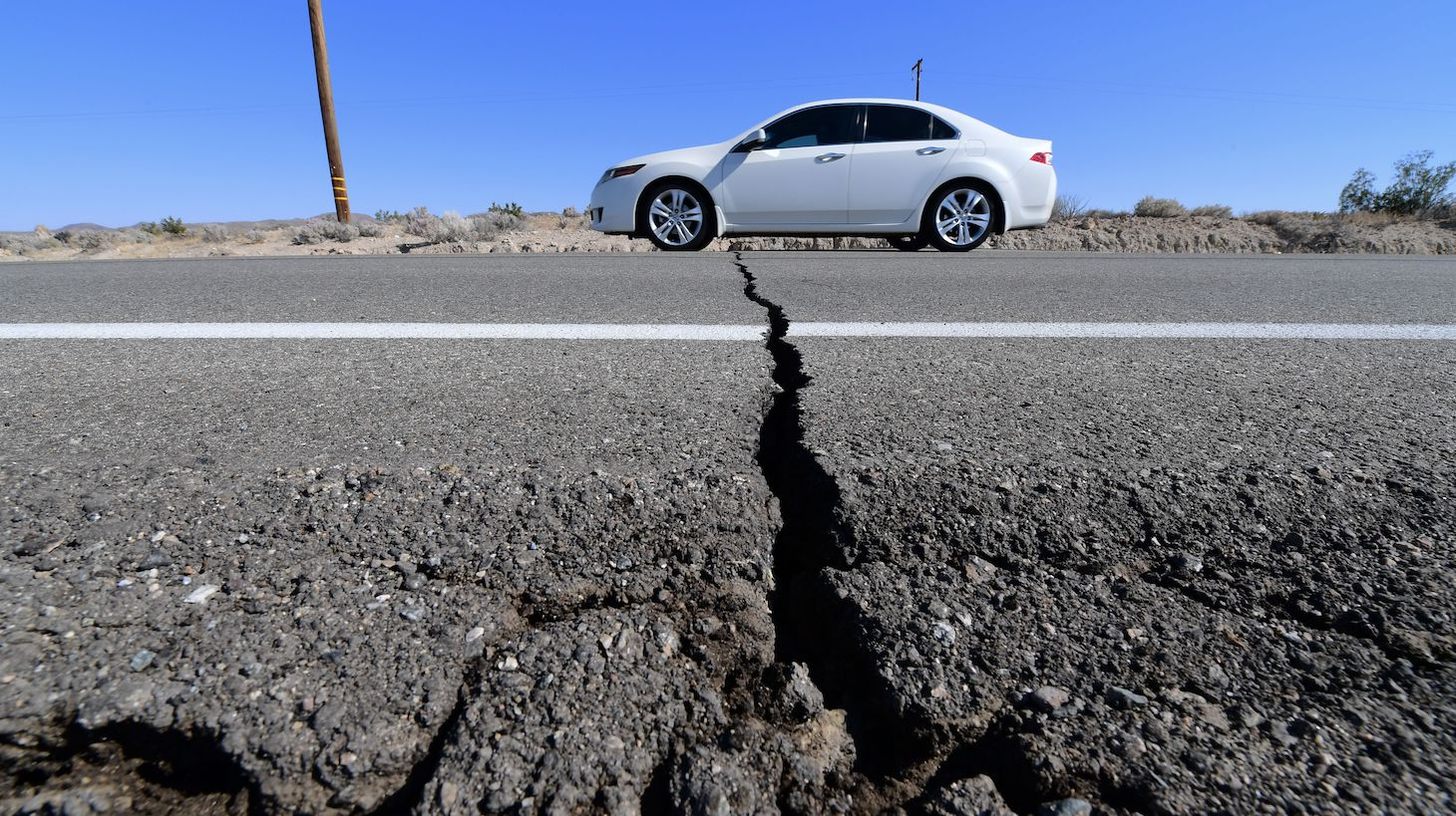 TOPSHOT - A car drives past a crack in the road on Highway 178, south of Trona, after a 6.4-magnitude earthquake hit in Ridgecrest, California, on July 4, 2019. - Southern California was rocked by a 6.4-magnitude earthquake Thursday morning, the US Geological Survey said, with authorities warning that the temblor, the largest in two decades, might not be the day's last. (Photo by FREDERIC J. BROWN / AFP) (Photo by FREDERIC J. BROWN/AFP via Getty Images)