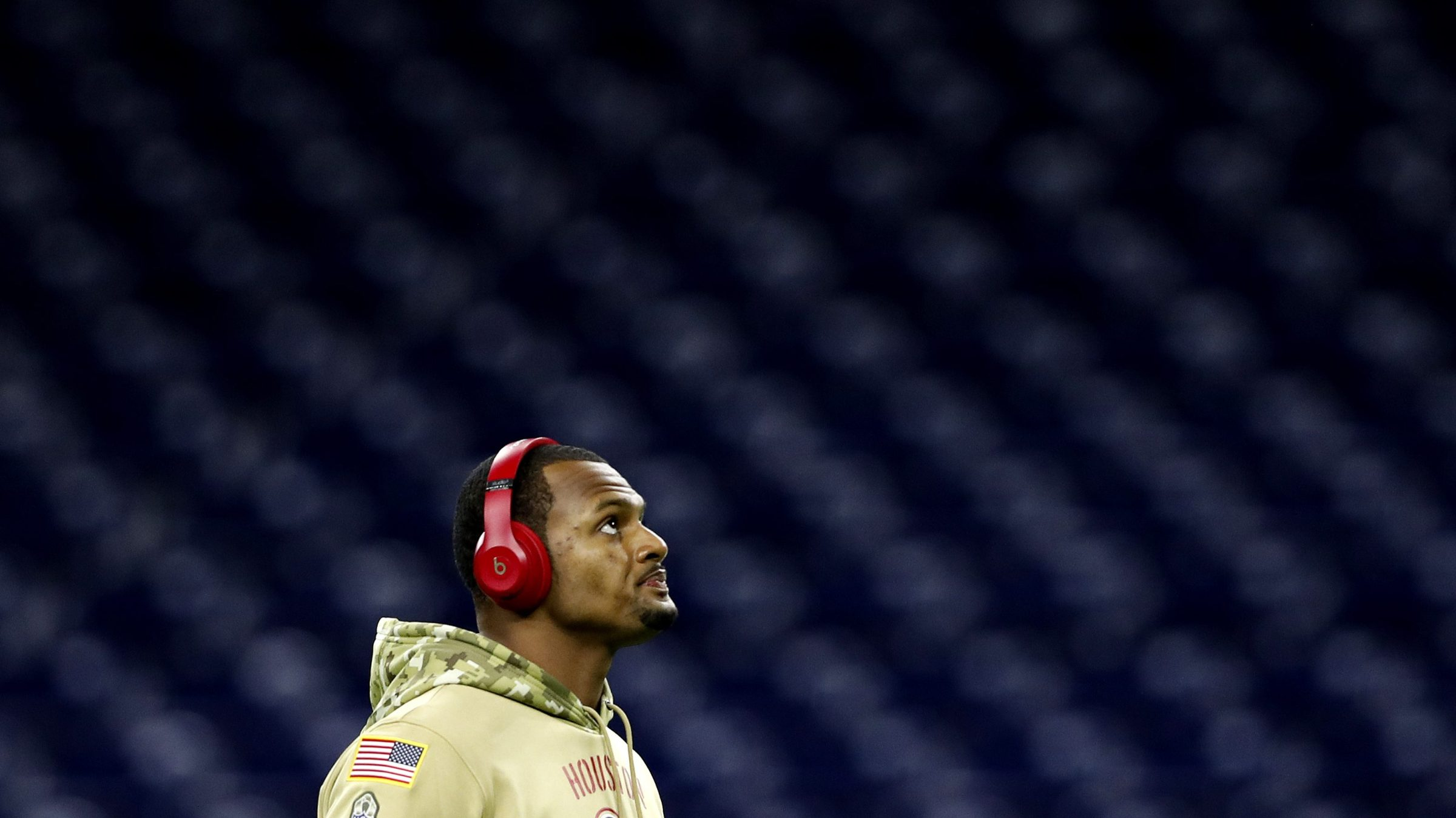 Deshaun Watson #4 of the Houston Texans warms up prior to the game against the New England Patriots at NRG Stadium on December 01, 2019 in Houston, Texas. He is in a green camo hoodie and wearing red headphone.