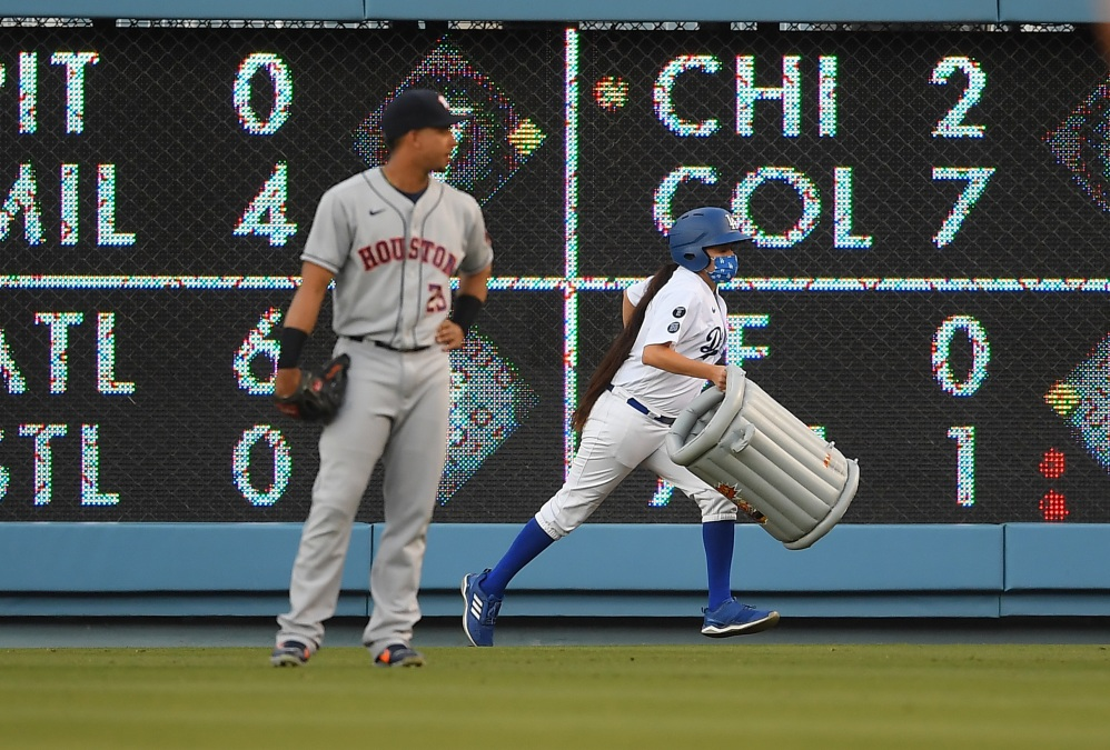 Michael Brantley watches as a bat girl removes an inflatable trash can