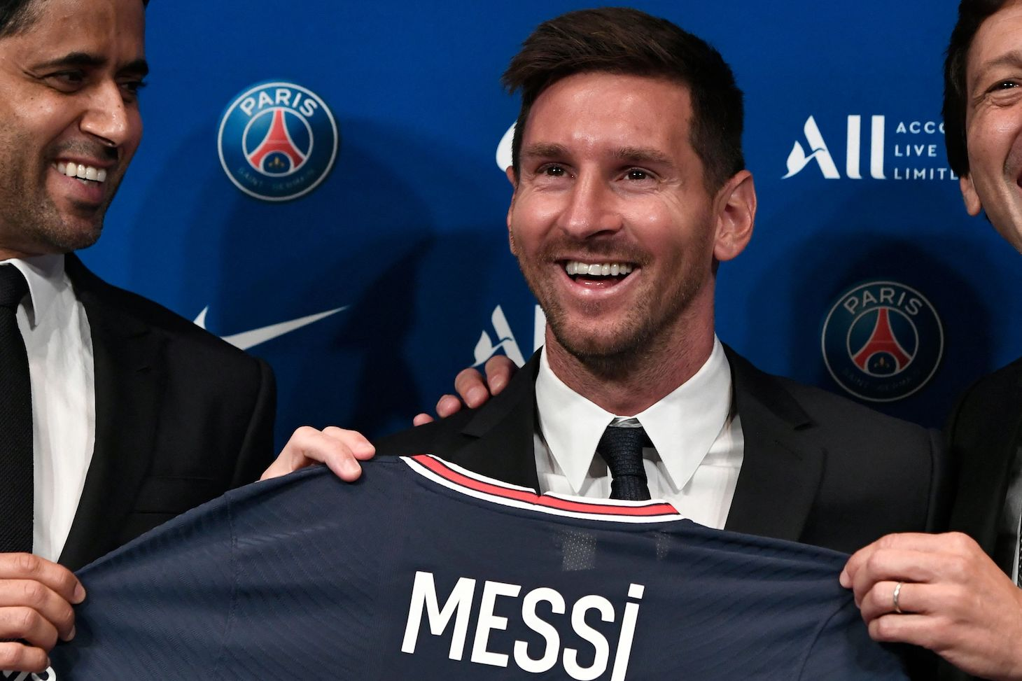 Paris Saint-Germain's Qatari President Nasser Al-Khelaifi (L) and Paris Saint-Germain's Sporting Director Leonardo Nascimento de Araujo (R) pose along side Argentinian football player Lionel Messi (C) as he holds-up his number 30 shirt during a press conference at the French football club Paris Saint-Germain's (PSG) Parc des Princes stadium in Paris on August 11, 2021. - The 34-year-old superstar signed a two-year deal with PSG on August 10, 2021, with the option of an additional year, he will wear the number 30 in Paris, the number he had when he began his professional career at Spain's Barca football club.