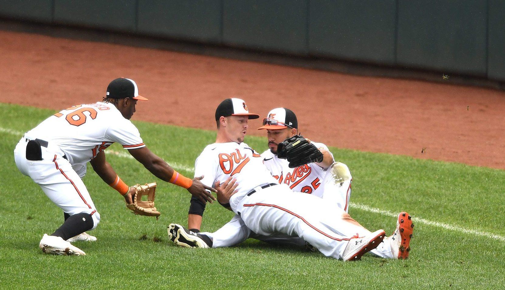 Some Baltimore Orioles crash into each other