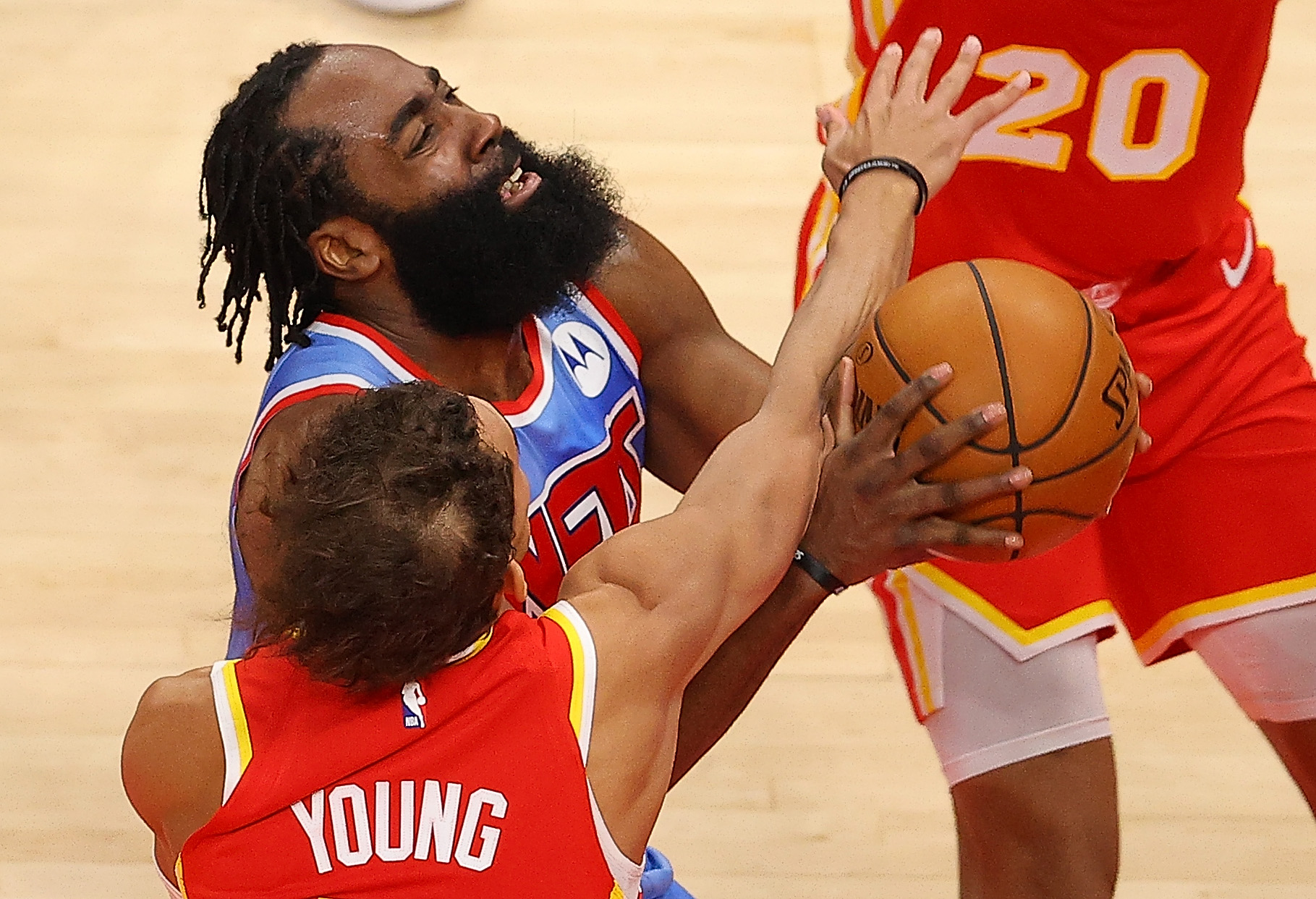 James Harden of the Brooklyn Nets is fouled by Trae Young of the Atlanta Hawks.