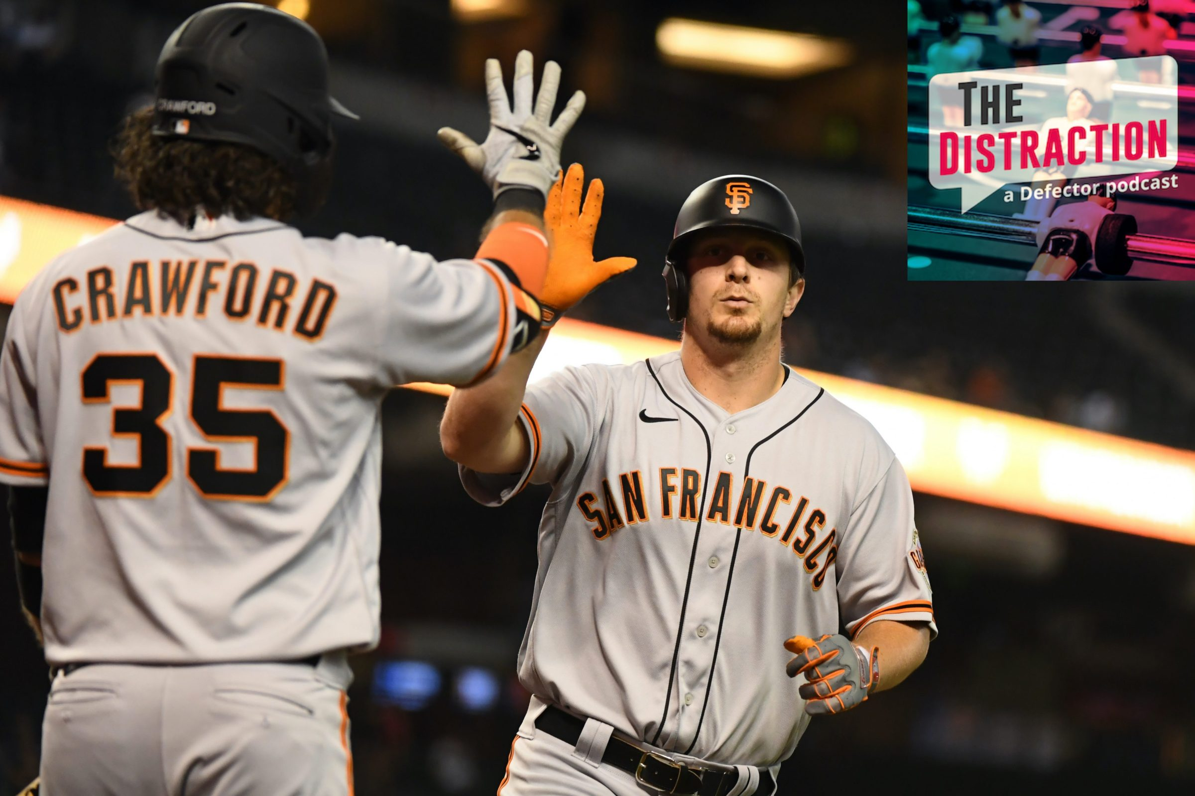Alex Dickerson and Brandon Crawford congratulate each other at home plate, presumably for being talked about on this episode of The Distraction.