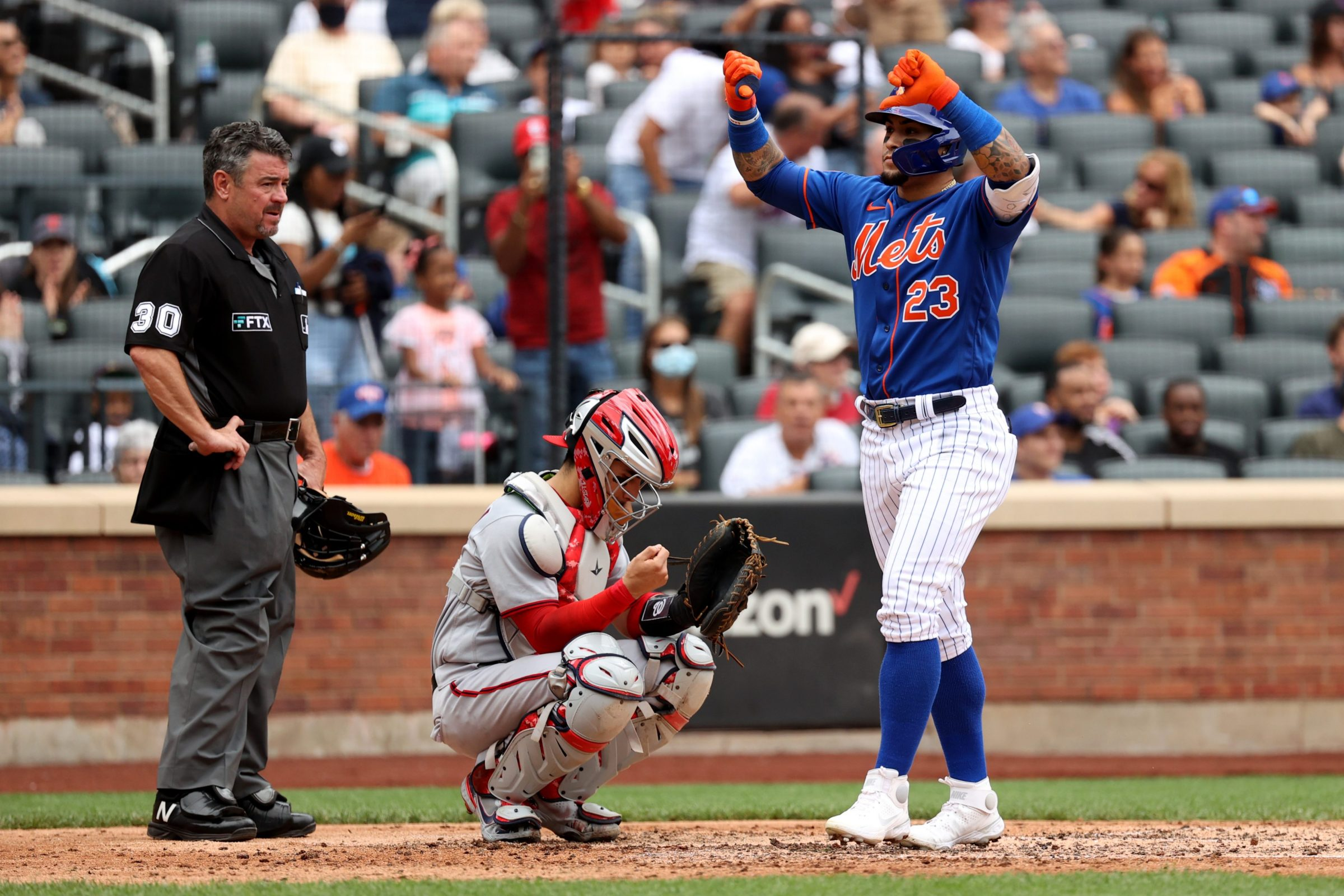 Javier Baez does a double thumbs-down gesture, apparently directed at Mets fans, after hitting a home run on Sunday against the Nationals.