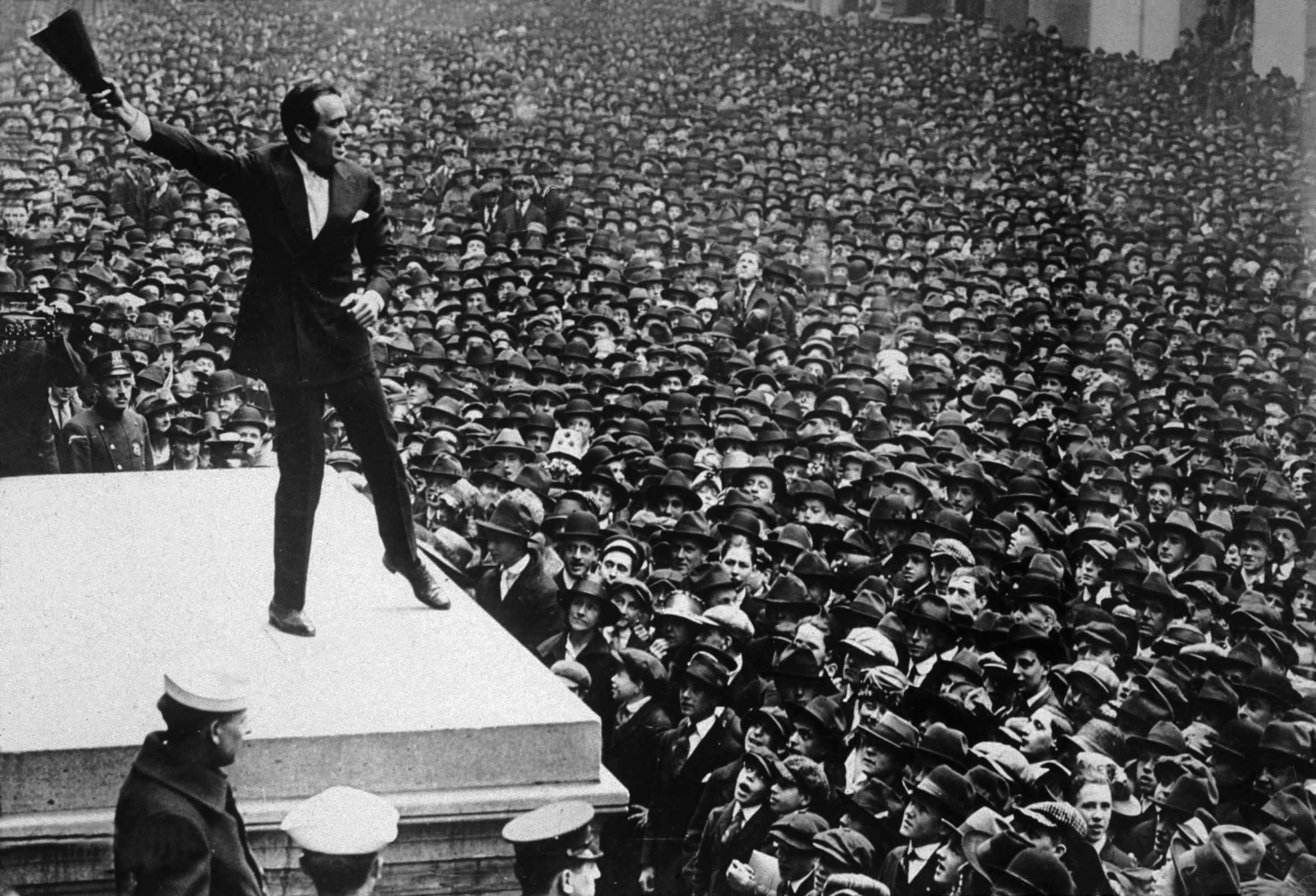 Full-length image of American actor Douglas Fairbanks Sr. waving a megaphone in the air while speaking from the Sub Treasury Building New York, to a sea of people, during a war bond rally, World War I.