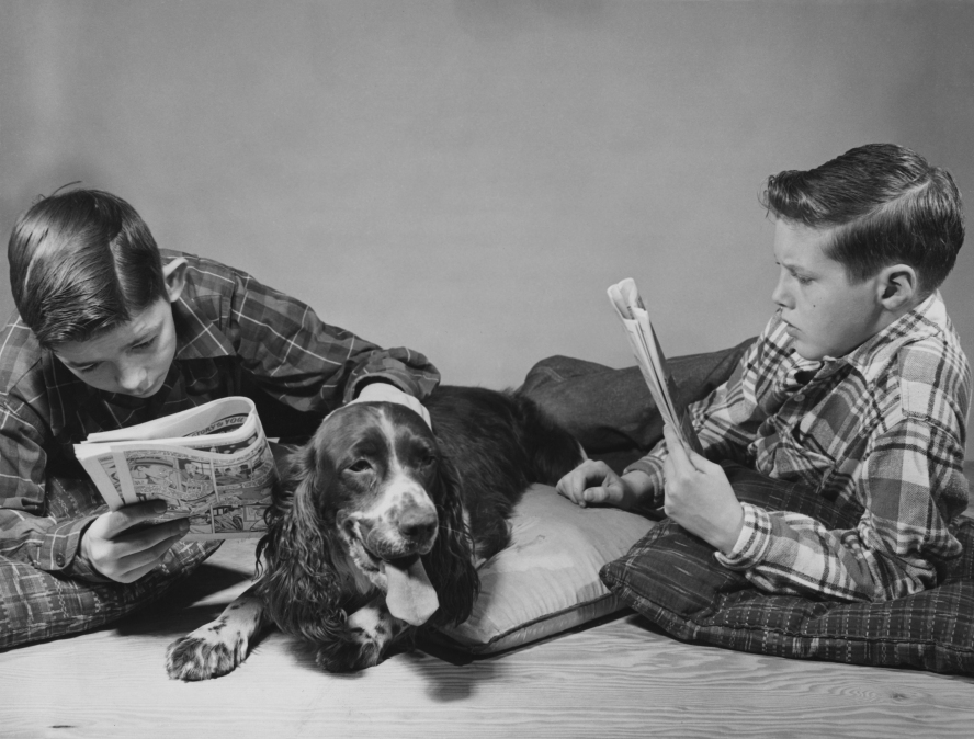 Two American boys reading comics in the company of a pet spaniel, circa 1955.