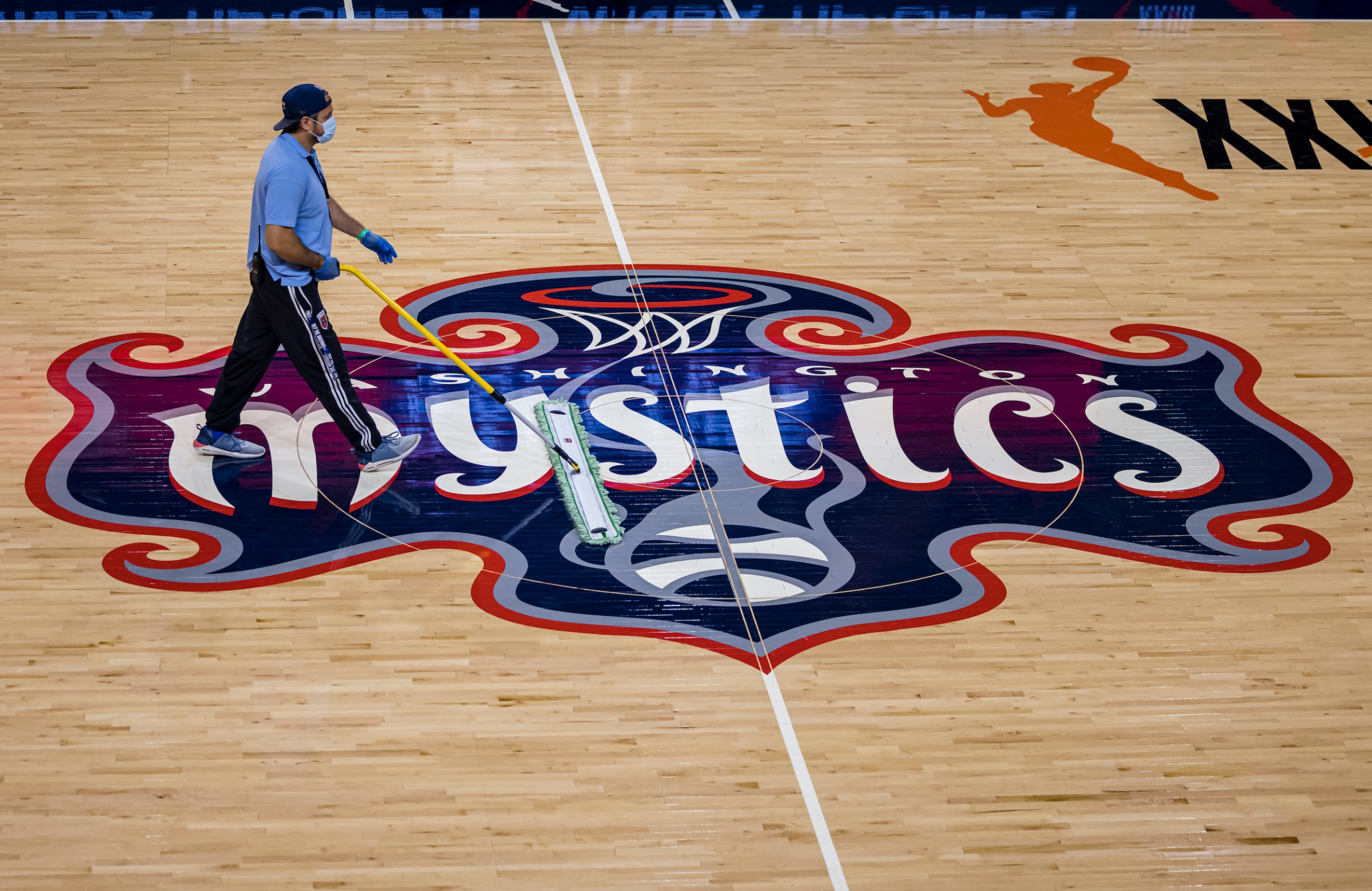 A worker sweeps the court before the second half of the game between the Washington Mystics and the Chicago Sky at Entertainment & Sports Arena on May 15, 2021 in Washington, DC.