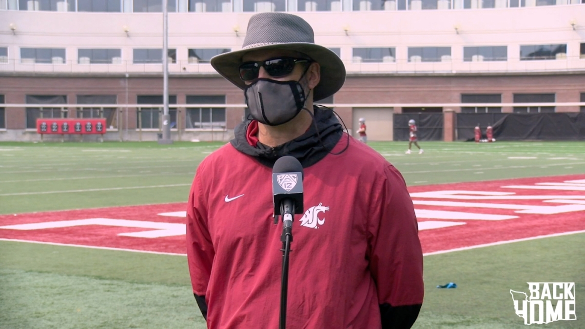 Washington State football coach Nick Rolovich addresses the media in a mask.