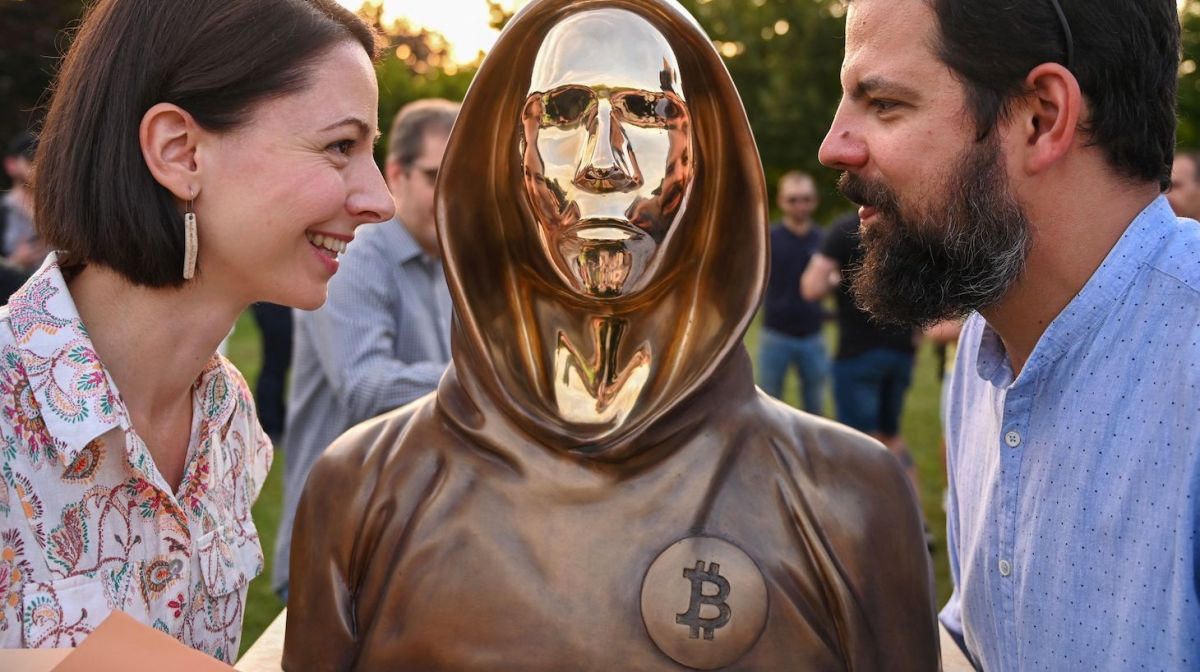 Hungarian sculptors and creators Reka Gergely (L) and Tamas Gilly (R) pose next to the statue of Satoshi Nakamoto, the mysterious inventor of the virtual currency bitcoin, after its unveiling at the Graphisoft Park in Budapest, on September 16, 2021. - Hungarian bitcoin enthusiasts unveiled a statue on September 16 in Budapest that they say is the first in the world to honour Satoshi Nakamoto, the mysterious inventor of the virtual currency. The bronze life-size sculpture depicts a hooded figure with stylised facial features, alluding to Nakamoto, a pseudonym credited as bitcoin's founder, but whose identity remains unknown. (Photo by ATTILA KISBENEDEK / AFP) (Photo by ATTILA KISBENEDEK/AFP via Getty Images)