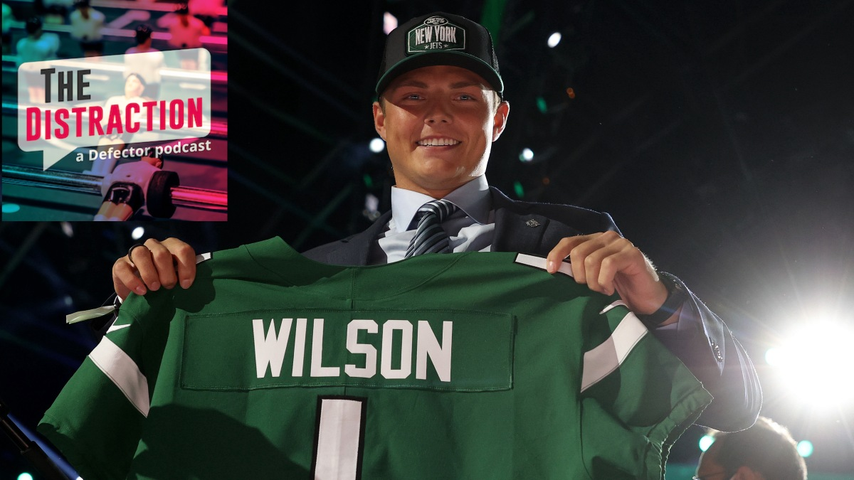 Jets quarterback Zach Wilson holding up his jersey on draft night, quite possibly the last time he will experience joy near such a jersey.