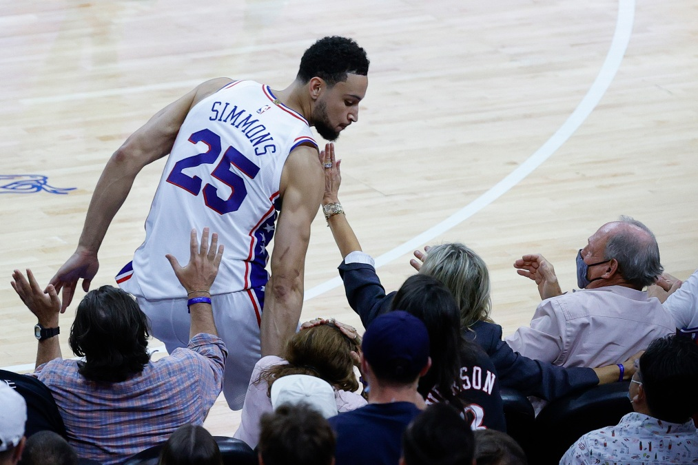Ben Simmons falls into the court-side seats.