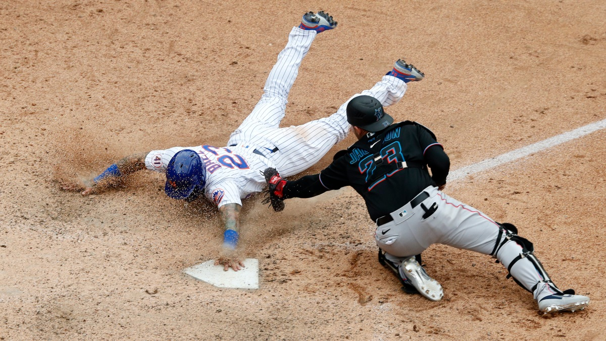 Javier Baez #23 of the New York Mets slides home with the game winning run in the ninth inning against Alex Jackson #23 of the Miami Marlins at Citi Field on August 31, 2021 in New York City.