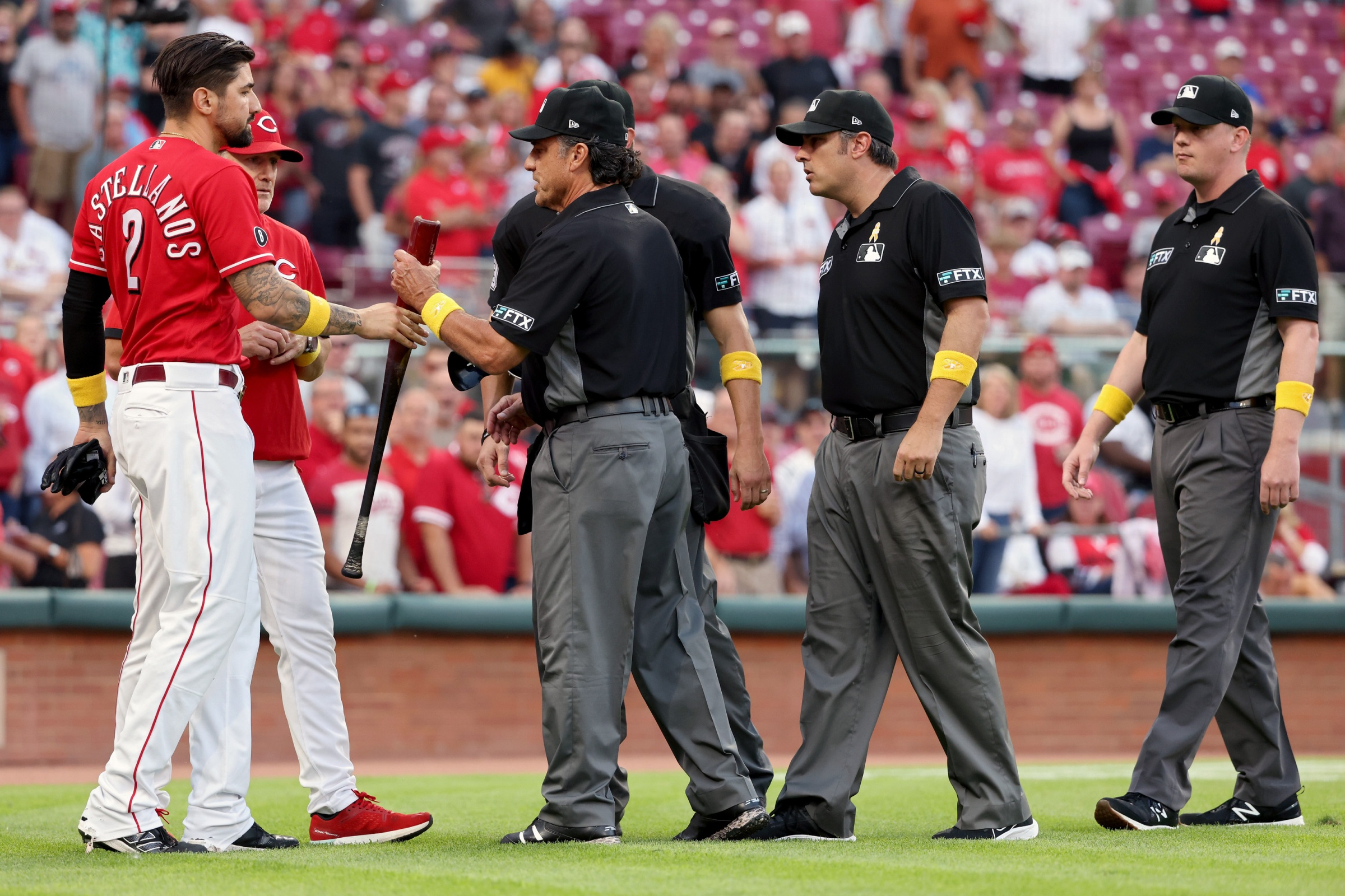 Umpires check the bat of Nick Castellanos after he destroys the St.Louis Cardinals.