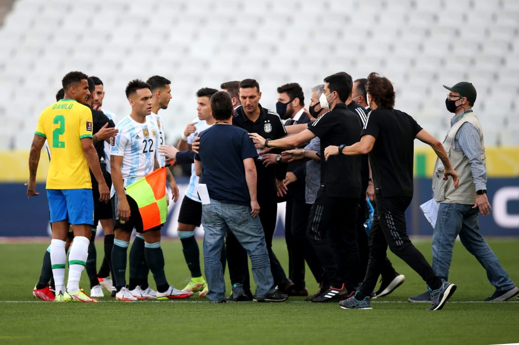 Health staff members argue with head coach of Argentina Lionel Scaloni and players of Brazil and Argentina during a match.