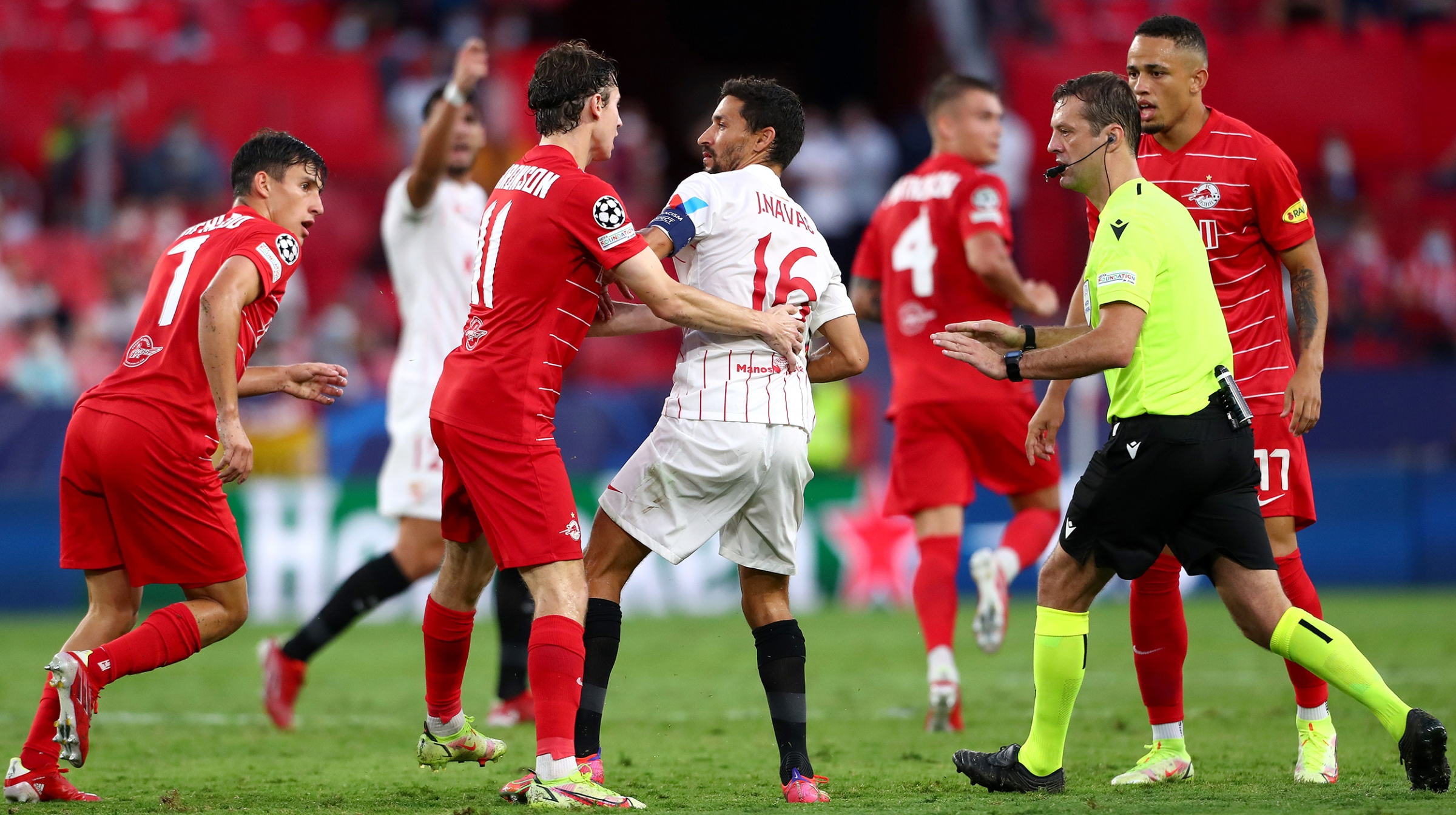 Brenden Aaronson of RB Salzburg interacts with Jesus Navas of Sevilla FC during the UEFA Champions League group G match between Sevilla FC and RB Salzburg at Estadio Ramon Sanchez Pizjuan on September 14, 2021 in Seville, Spain.