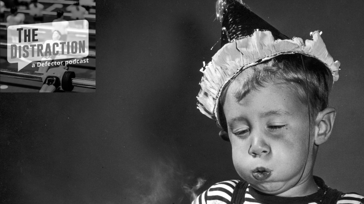 circa 1945: Studio image of a young boy wearing a party hat, blowing out the four candles on a chocolate birthday cake