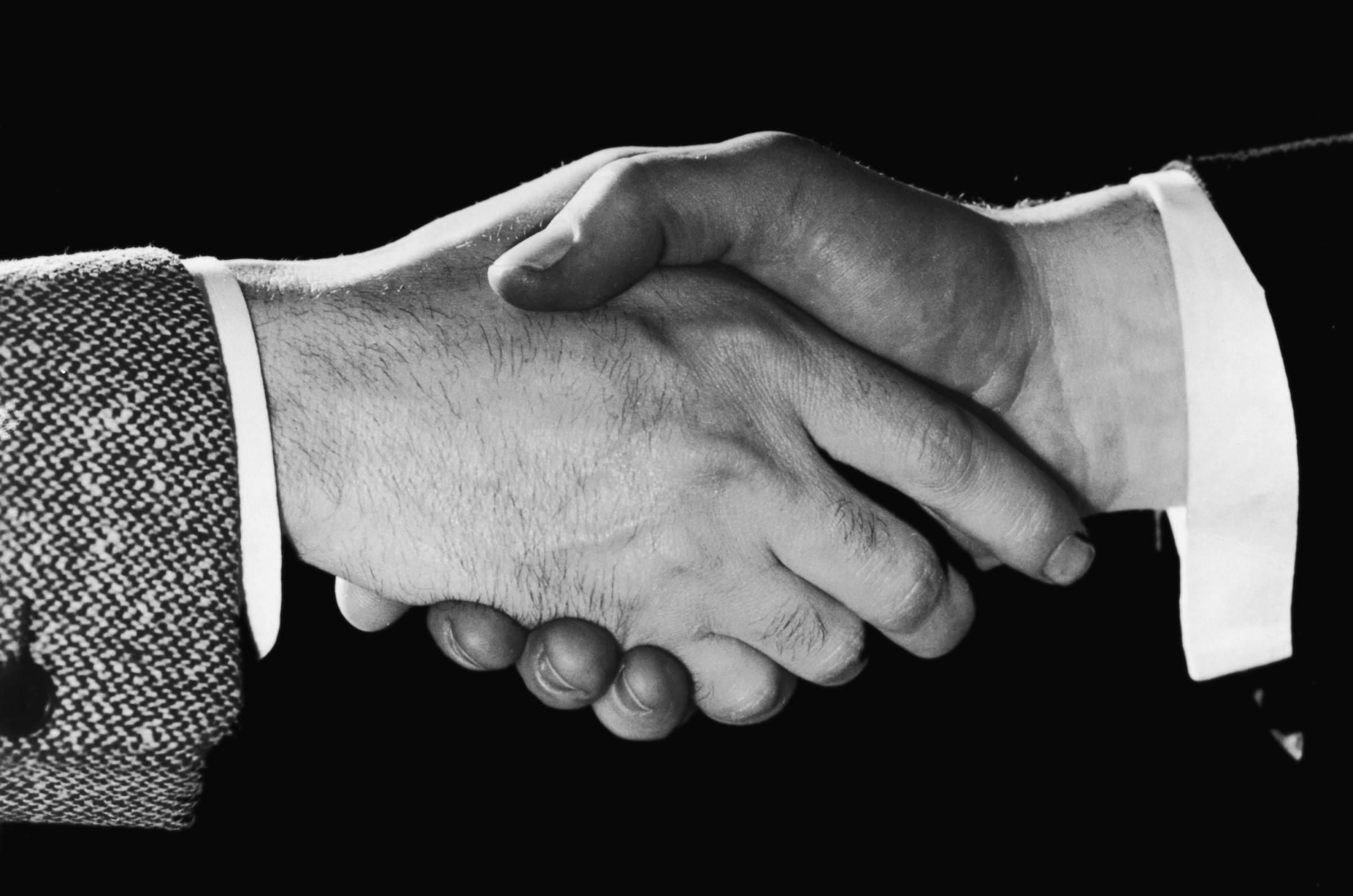 A close-up of two men shaking hands, circa 1948.