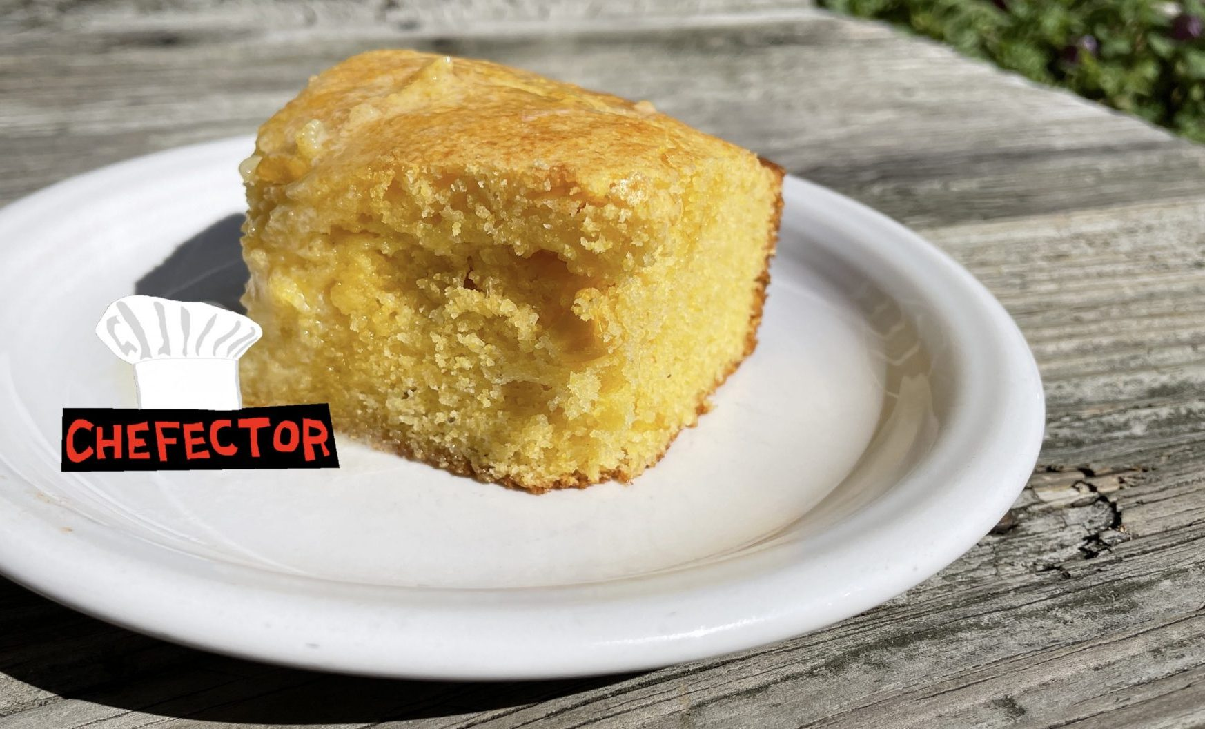 A hunk of cornbread on a plate on a rustic tabletop