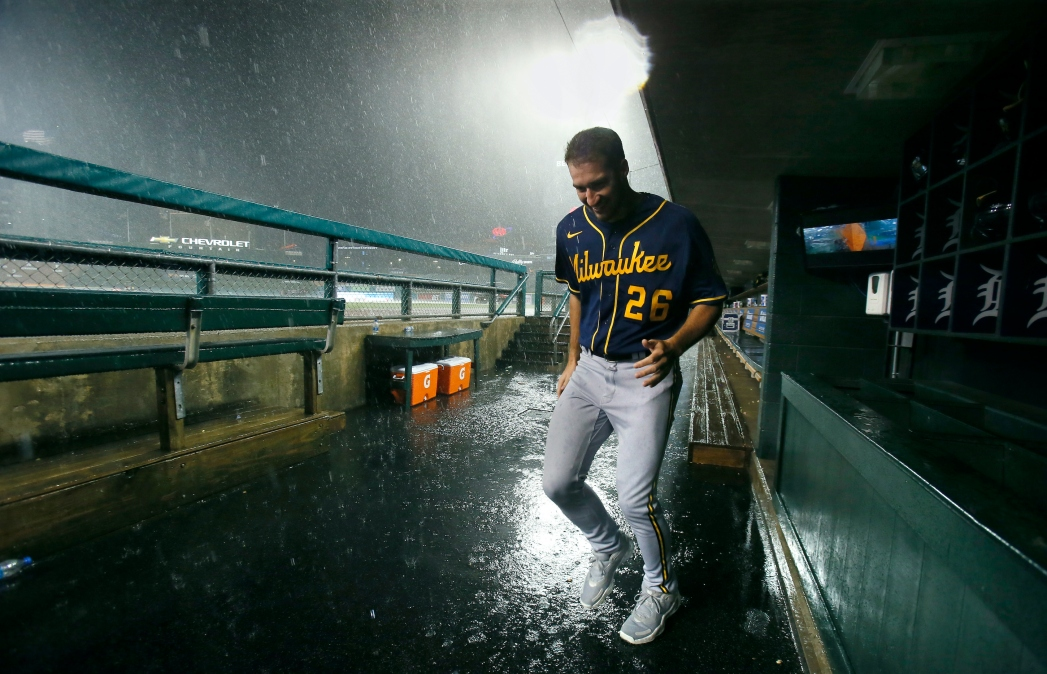 Pitcher Aaron Ashby #26 of the Milwaukee Brewers tries to stay dry as he leaves the dugout as a thunderstorm moves through the area following the sixth inning of a game against the Detroit Tigers at Comerica Park on September 14, 2021, in Detroit, Michigan.