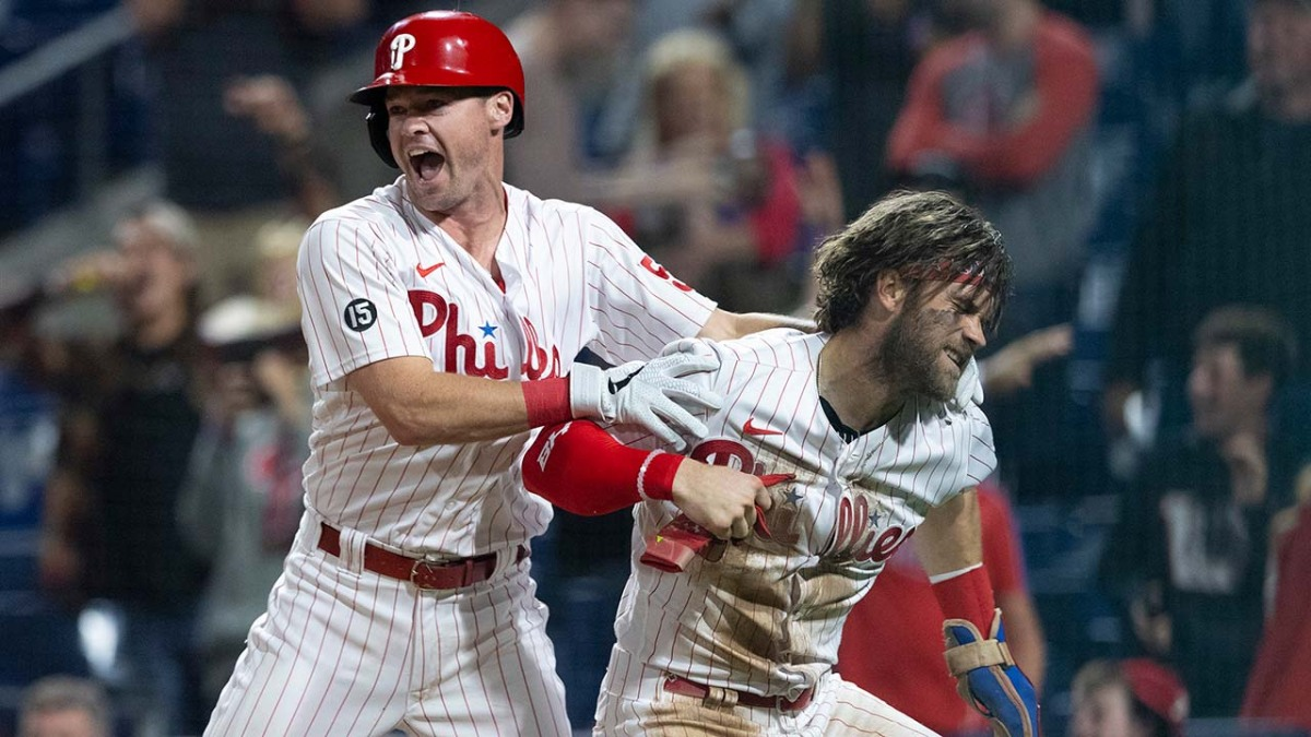 Bryce Harper looks kinda angry when celebrating, while Andrew Knapp hugs him from behind. They're clearly at home plate, and fans behind them are excited