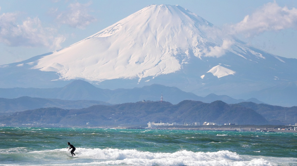 TOKYO, JAPAN - JANUARY 30: A local surfer is seen in action with Mount Fuji in the background from the beach of Enoshima during the build up to the Tokyo 2020 Olympic Games on January 30, 2020 in Fujisawa, Kanagawa Prefecture, Japan. The venue will hold the sailing events. (Photo by Clive Rose/Getty Images)