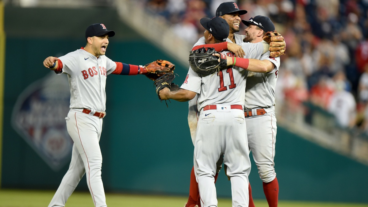 Jose Iglesias #12, Xander Bogaerts #2, Rafael Devers #11 and Kyle Schwarber #18 of the Boston Red Sox celebrate after a 7-5 victory against the Washington Nationals at Nationals Park on October 03, 2021 in Washington, DC.