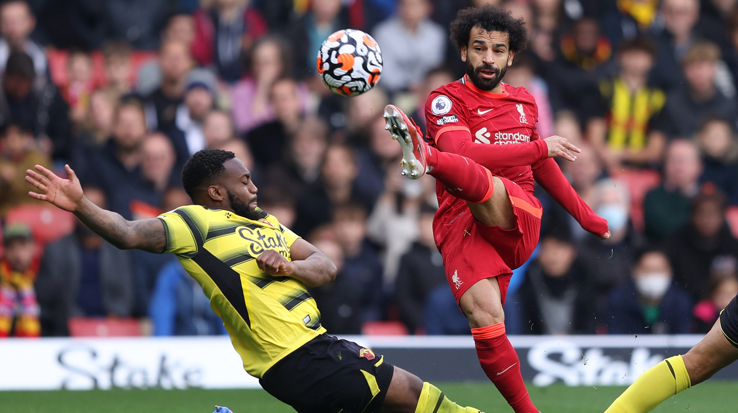 Mohamed Salah of Liverpool takes a shot as Danny Rose of Watford FC attempts to block during the Premier League match between Watford and Liverpool at Vicarage Road on October 16, 2021 in Watford, England.