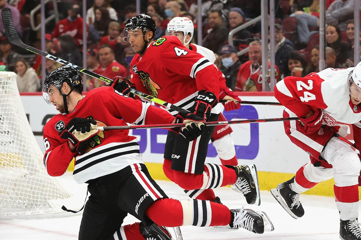 CHICAGO, ILLINOIS - OCTOBER 24: Erik Gustafsson #56 of the Chicago Blackhawks falls after getting his stick caught around Pius Suter #24 of the Detroit Red Wings at United Center on October 24, 2021 in Chicago, Illinois. (Photo by Jonathan Daniel/Getty Images)