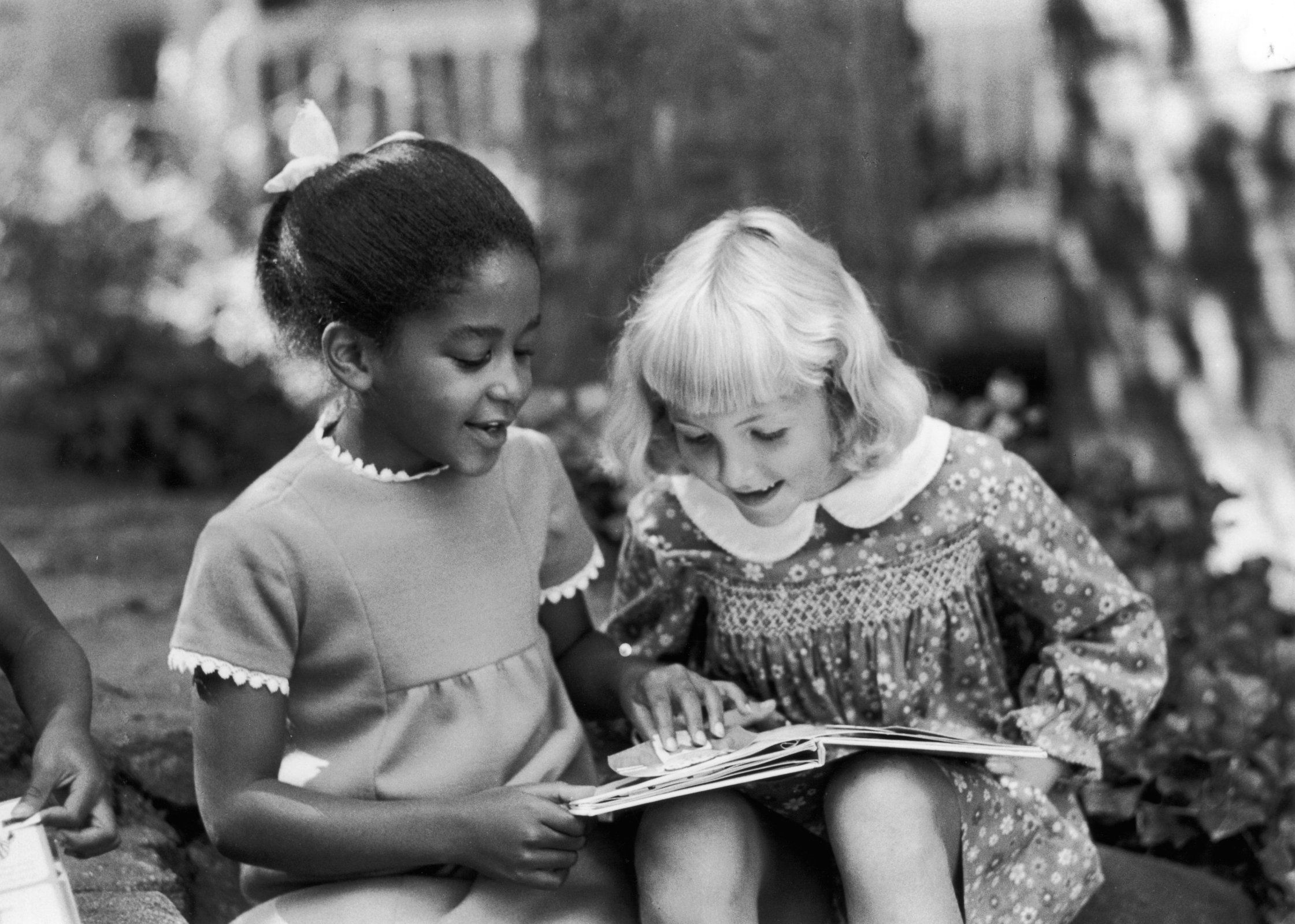 Two children read a book together.