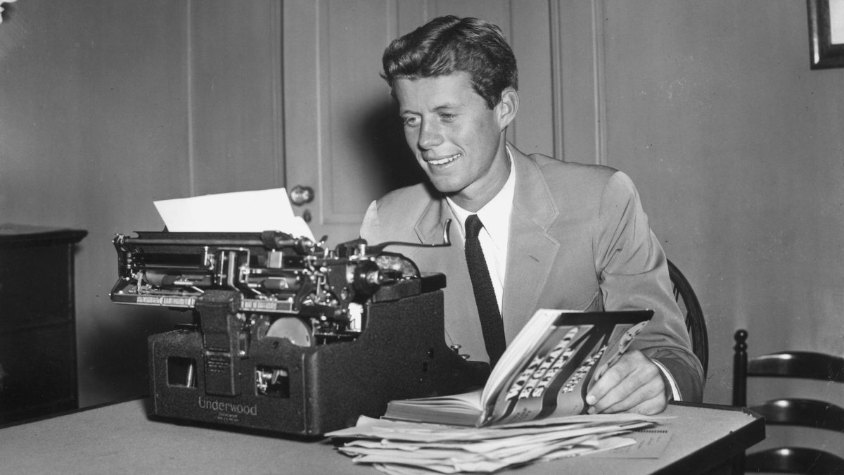 A young John F. Kennedy sits at a typewriter