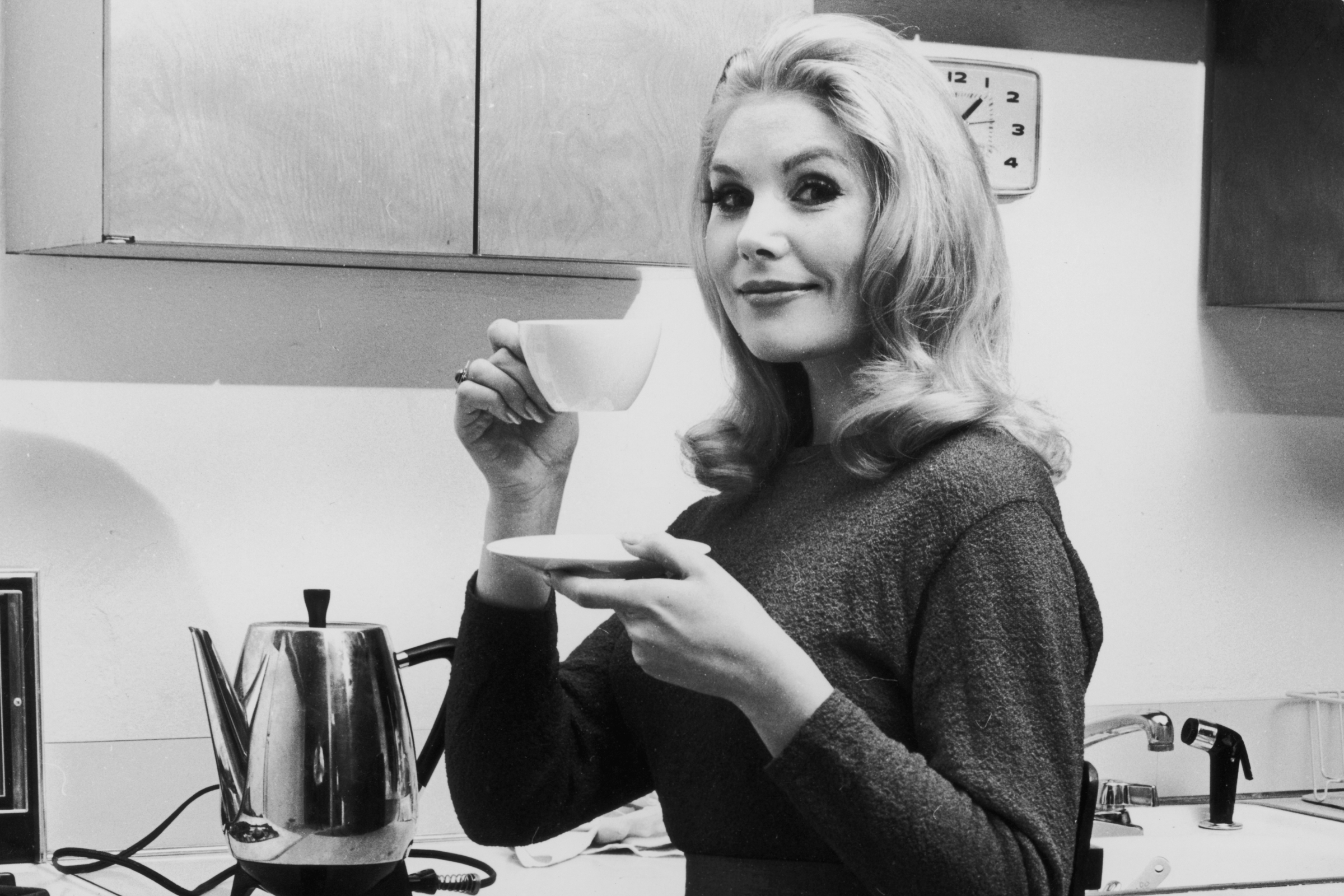 circa 1965: A woman lifts a cup of coffee off a saucer in a kitchen. (Photo by Leo Vals/Hulton Archive/Getty Images)