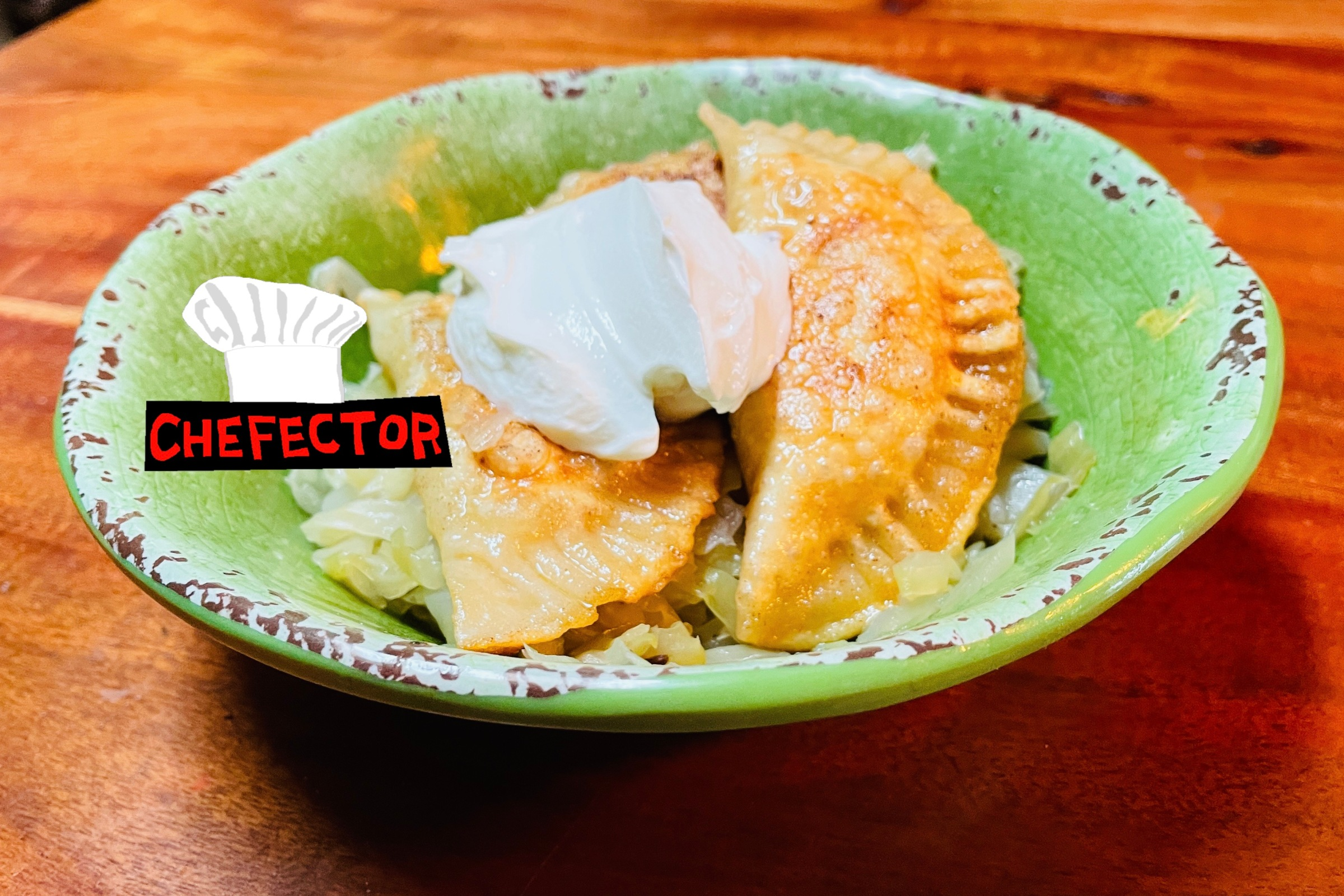 A bowl of pierogi with cabbage and sour cream